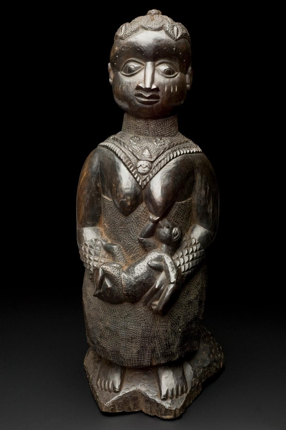 Carved figure of a woman breastfeeding, West Africa, 1890-1920