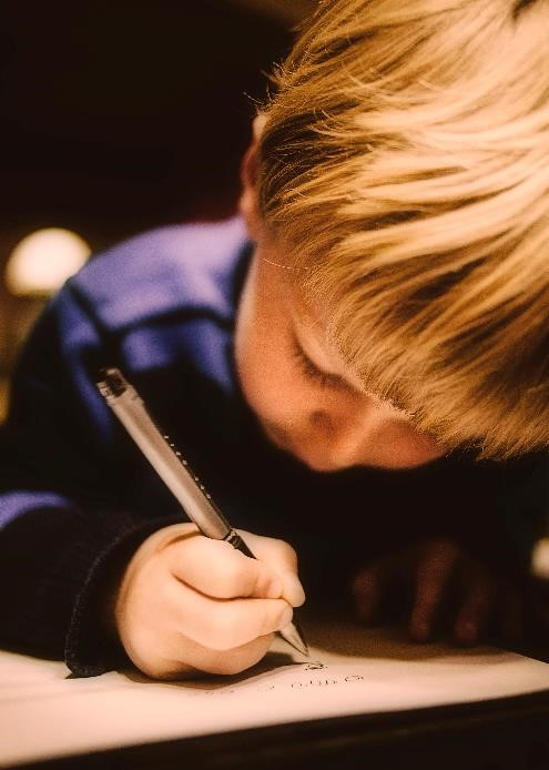 Child writing by hand with pencil