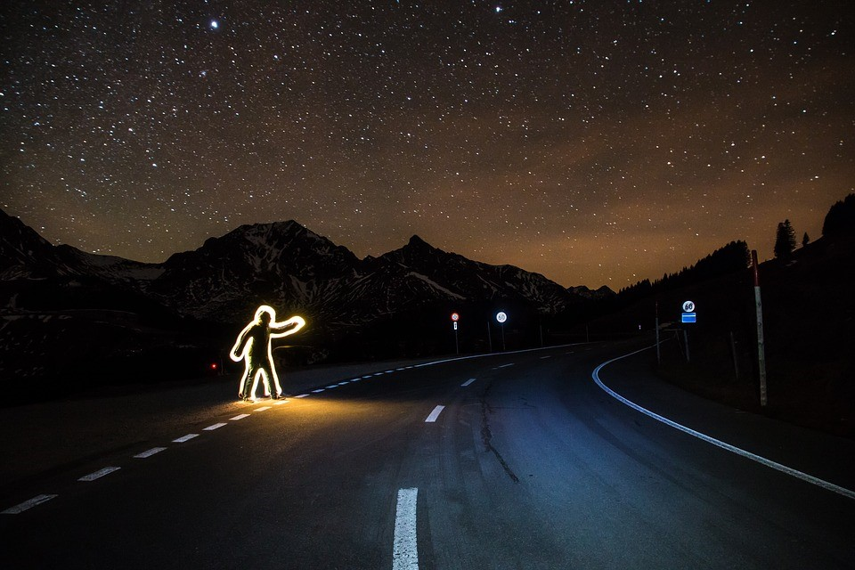 Luminous man crossing the road at night