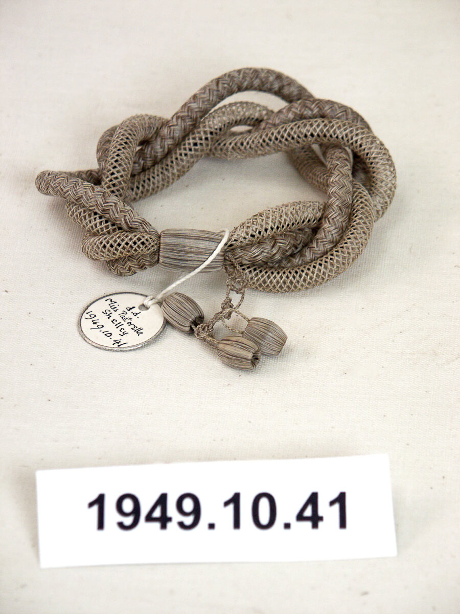 A bracelet fashioned from plaited and netted grey human hair of a deceased.