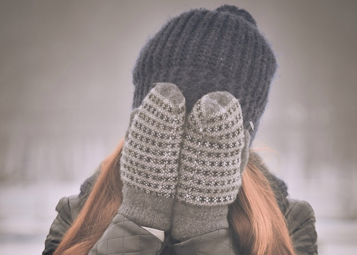 Woman covering her face with gloved hands
