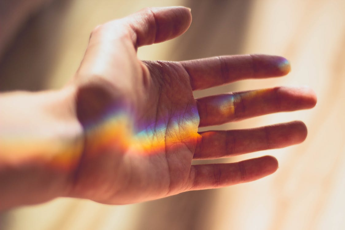 A hand with a rainbow projected on to it.