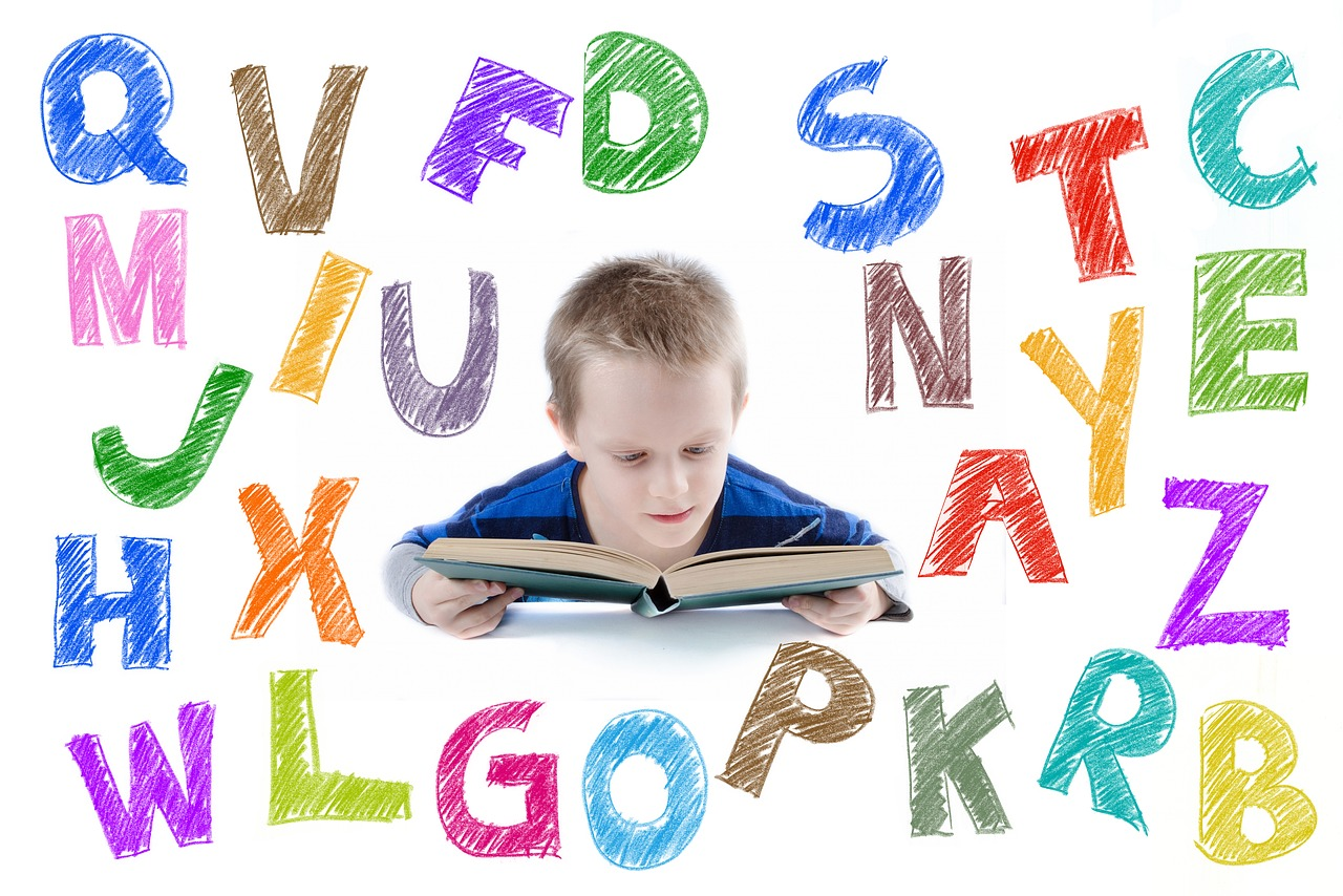 A child reading a book surrounded by graphics of colourful letters of the alphabet