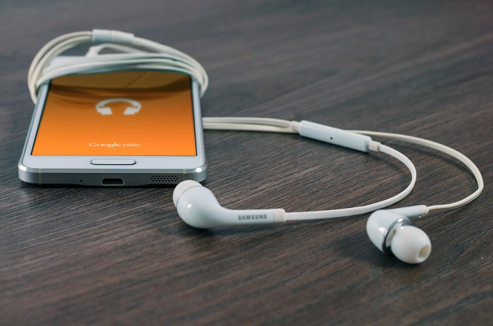 A smartphone with earbuds displays Google Play music streaming