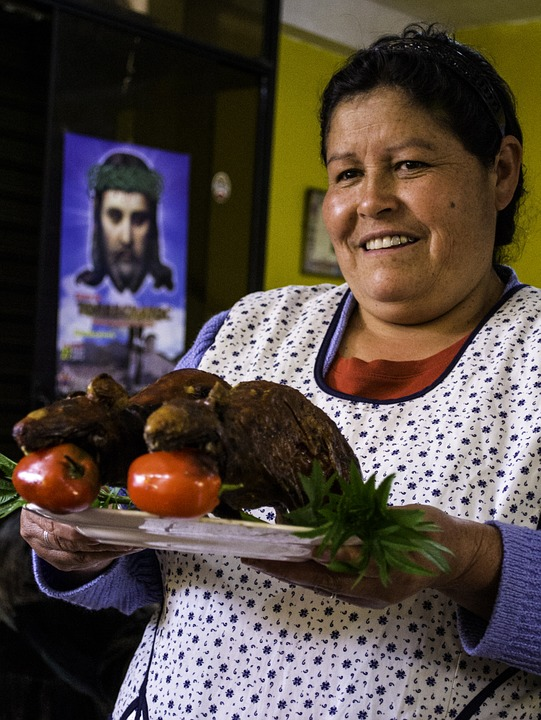 Woman serving cooked guinea pigs.