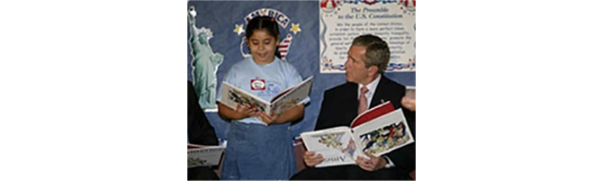 President George W. Bush with a childs book upside down