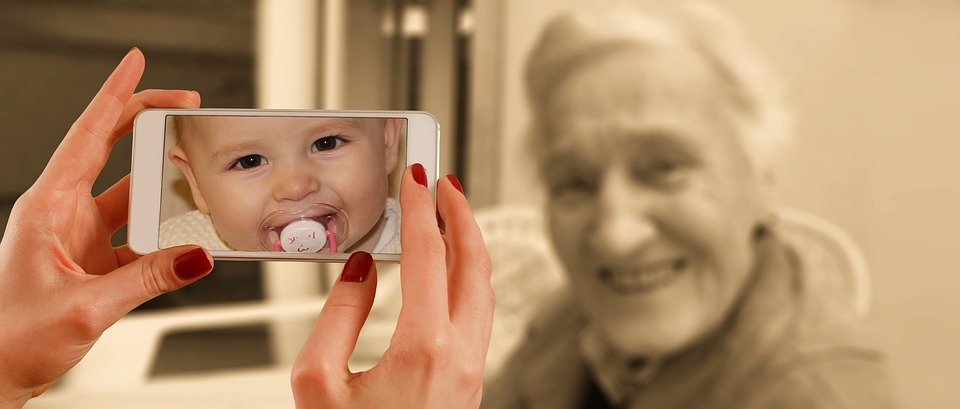 Image of elderly woman and hands holding a phone displaying a photo of a baby.