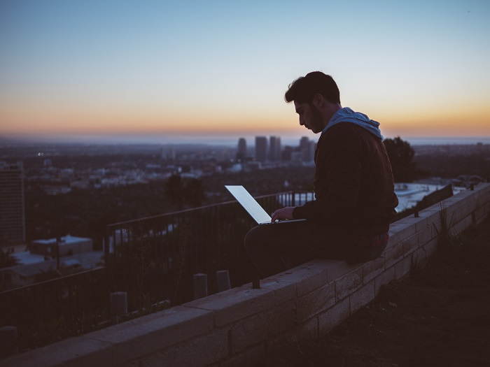 A young man works on a laptop while sitting on a city rooftop