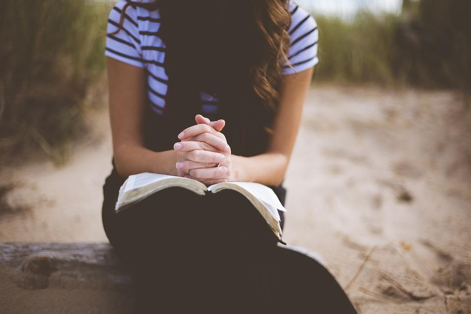 A girl praying on the beach.