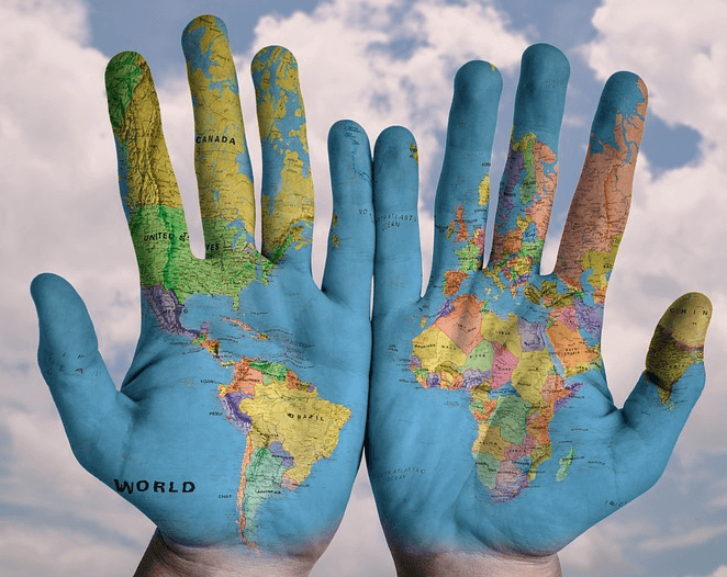 Two hands with a global map painted on it