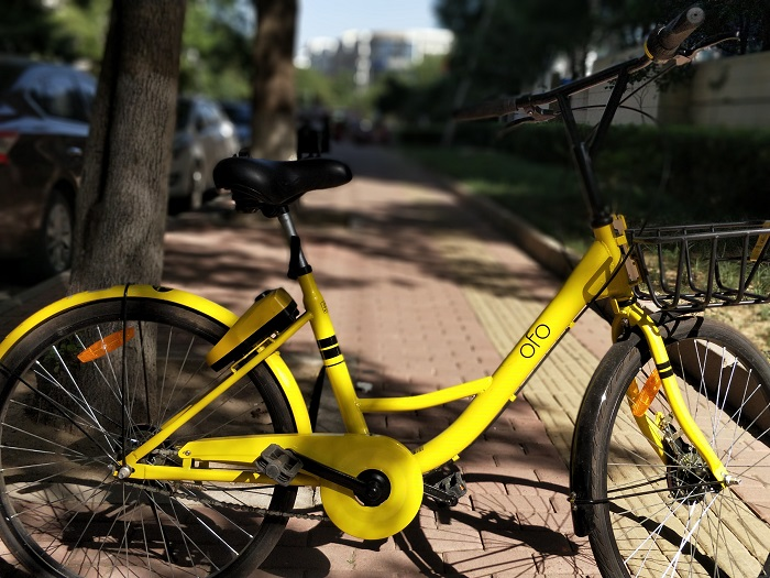 An Ofo bike share scheme bike is parked on a city street